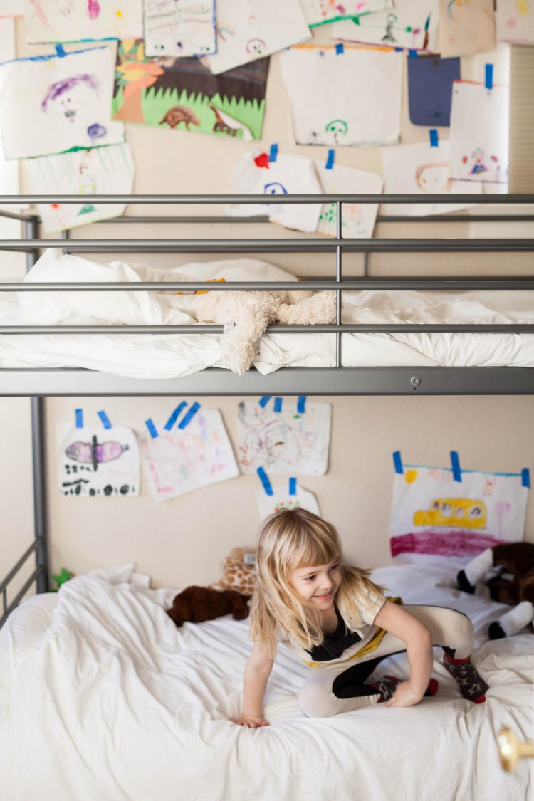 girl on bunkbed with kids wall art