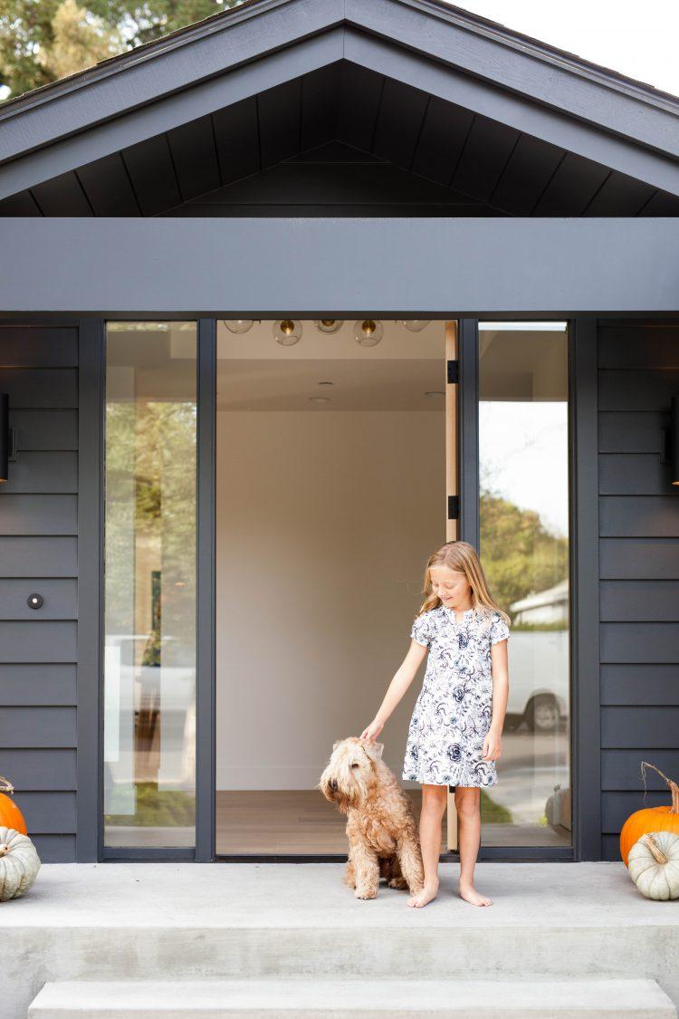 girl and dog outside a modern black house