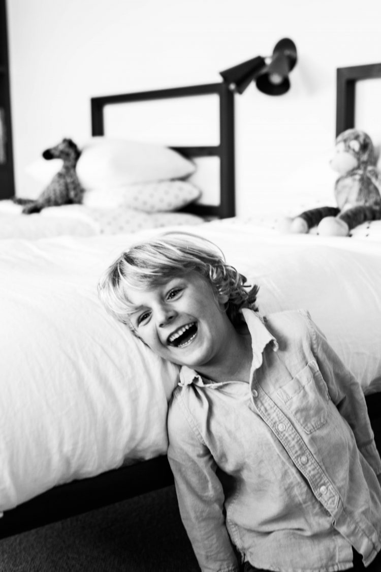 boy laughing on a bed in black and white