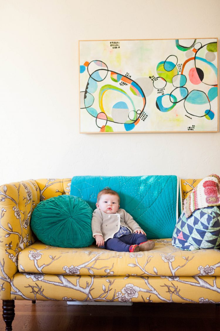 baby on a sofa  with modern wall art