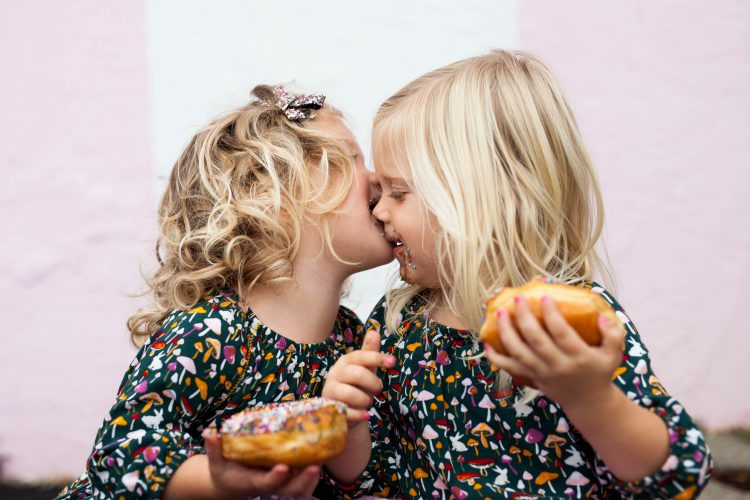 twins girls eating donuts