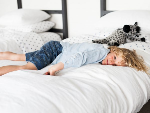 kid lying on white bed