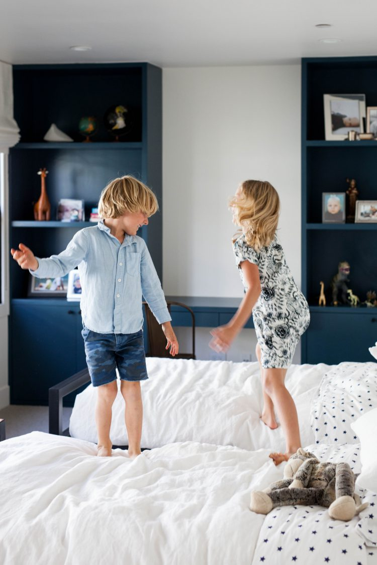 kids jumping on beds in modern home