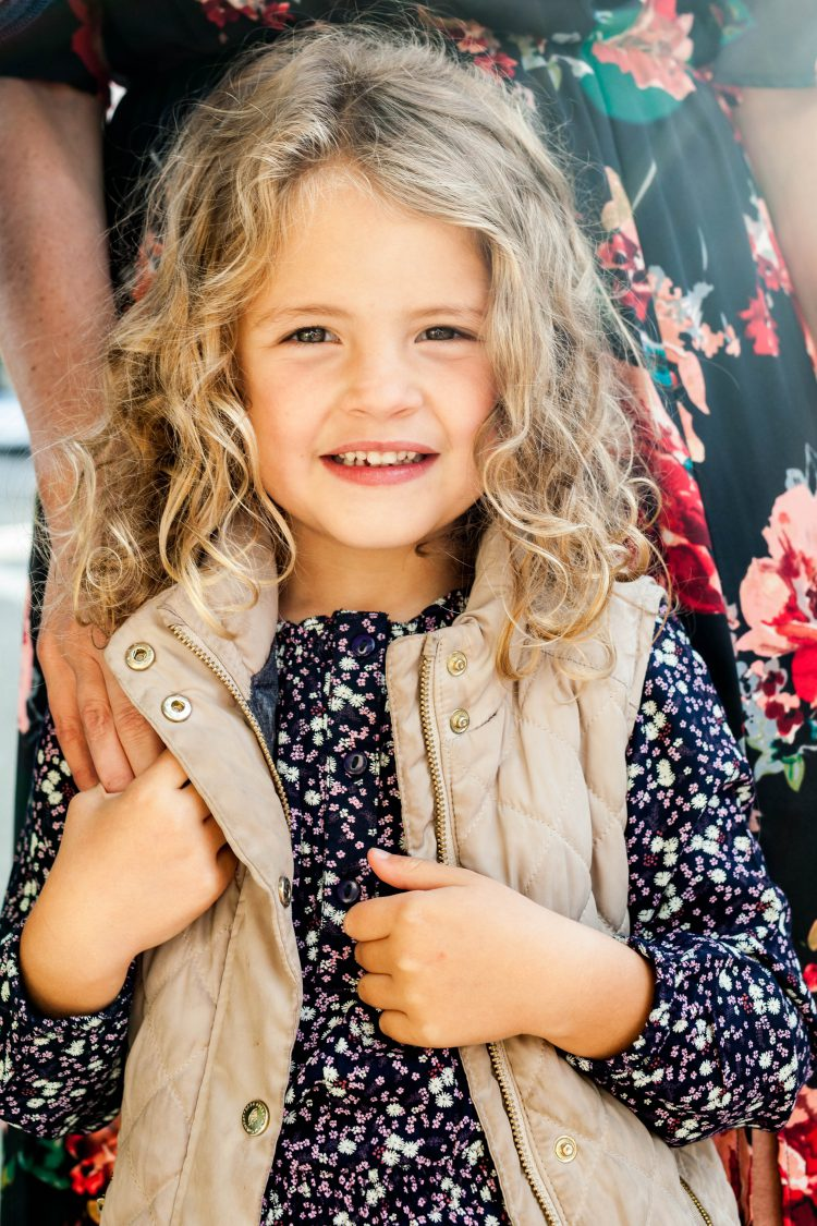 young girl wearing vest and floral shirt